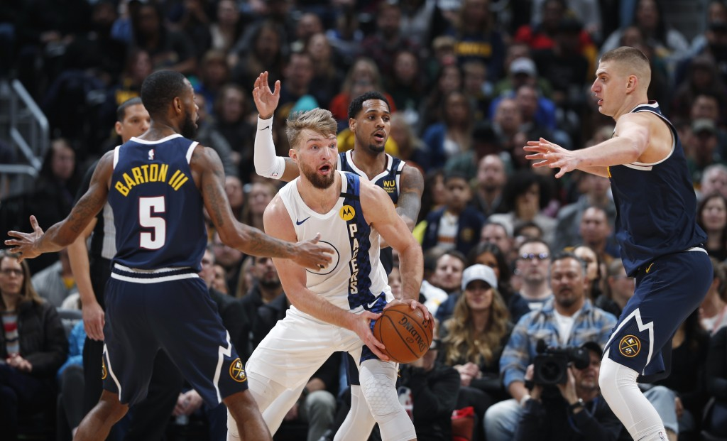 Indiana Pacers forward Domantas Sabonis, center, looks to pass the ball as, from left, Denver Nuggets guards Will Barton and Monte Morris and center N...