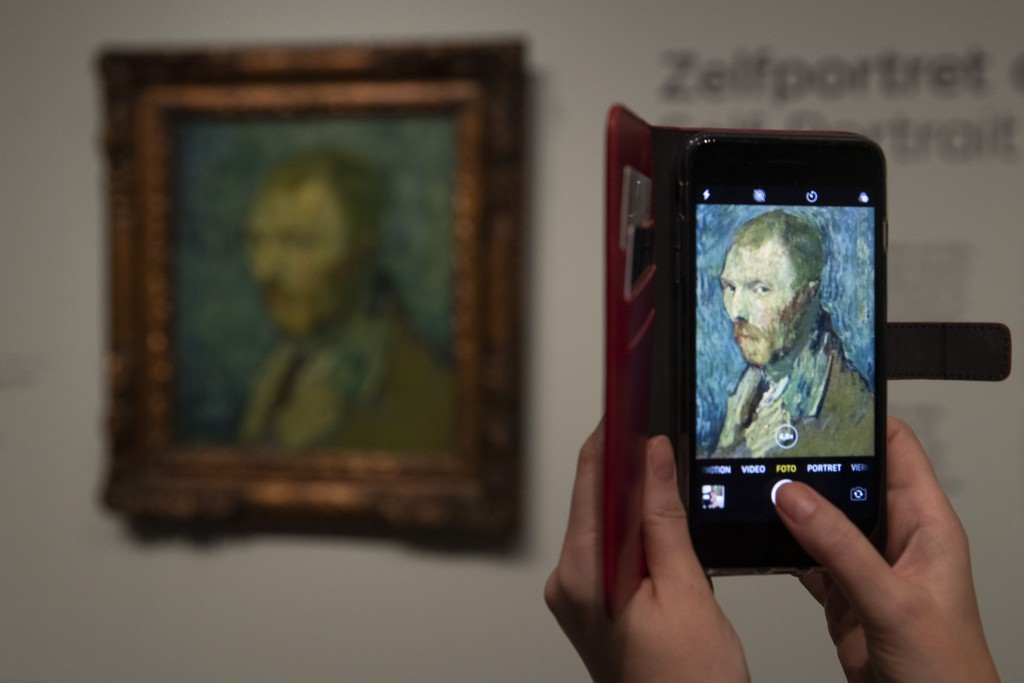 A journalist takes a picture of the previously contested painting by Dutch master Vincent van Gogh, a 1889 self-portrait, of which the authenticity wa...