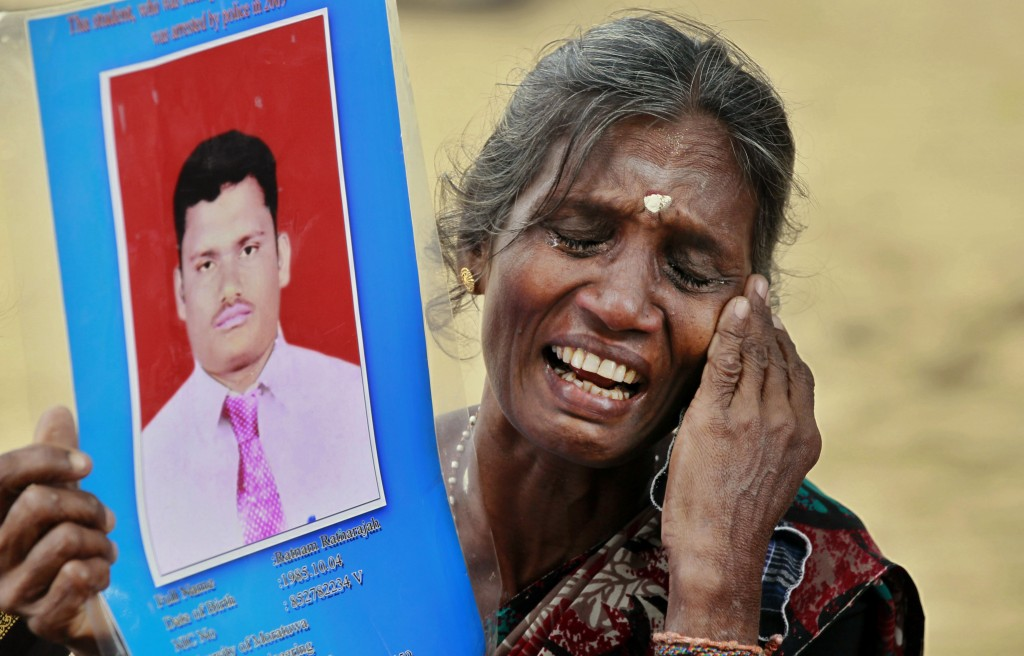 In this Friday, Nov. 15, 2013, file photo, a Sri Lankan ethnic Tamil woman cries holding a portrait of her missing son during a protest in Jaffna, Sri...