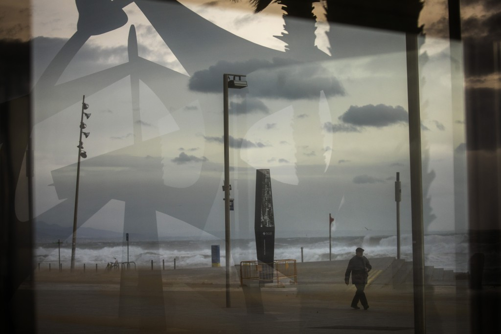 A man is seen through a window as he walks near the beach during strong winds in Barcelona, Spain, Monday, Jan. 20, 2020. Two people have died as stor...