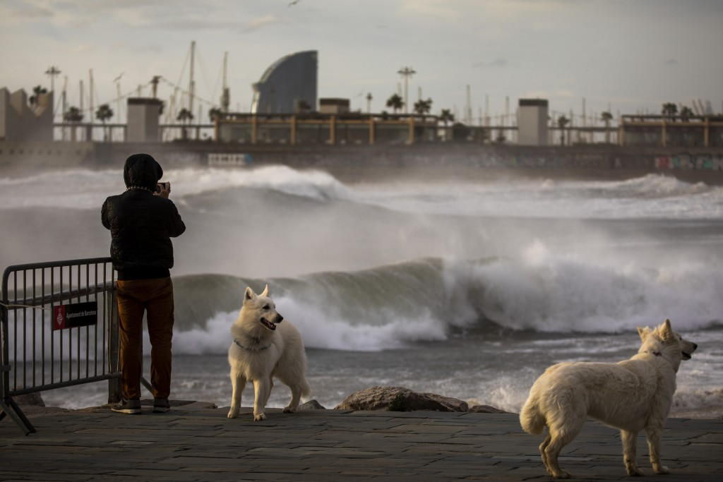A man photographs the Mediterranean sea during strong winds in Barcelona, Spain, Monday, Jan. 20, 2020. Two people have died as storms carrying heavy ...