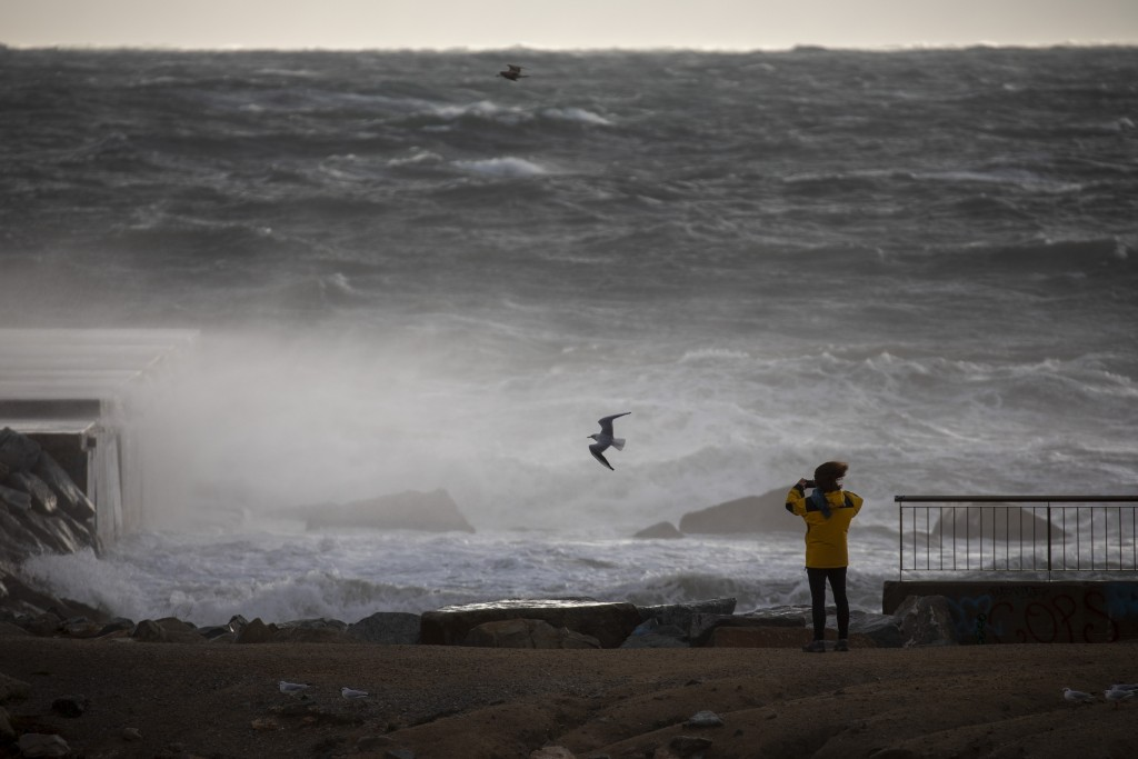A woman photographs the Mediterranean sea during strong winds in Barcelona, Spain, Monday, Jan. 20, 2020. Two people have died as storms carrying heav...