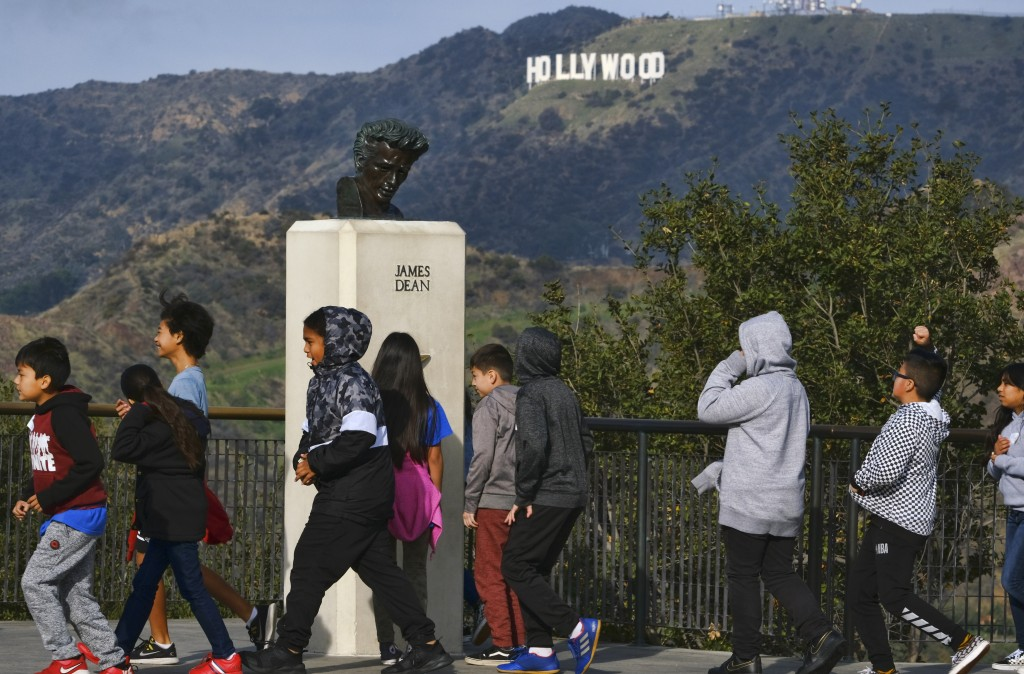 In this Friday, Jan. 17, 2020, photo, school children walk past a bust of actor James Dean during a field trip, at the Griffith Observatory in the Gri...