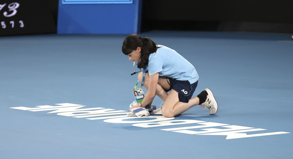 Court staff wipes water from Rod Laver Arena that was dripping from the roof during first round singles matches at the Australian Open tennis champion...