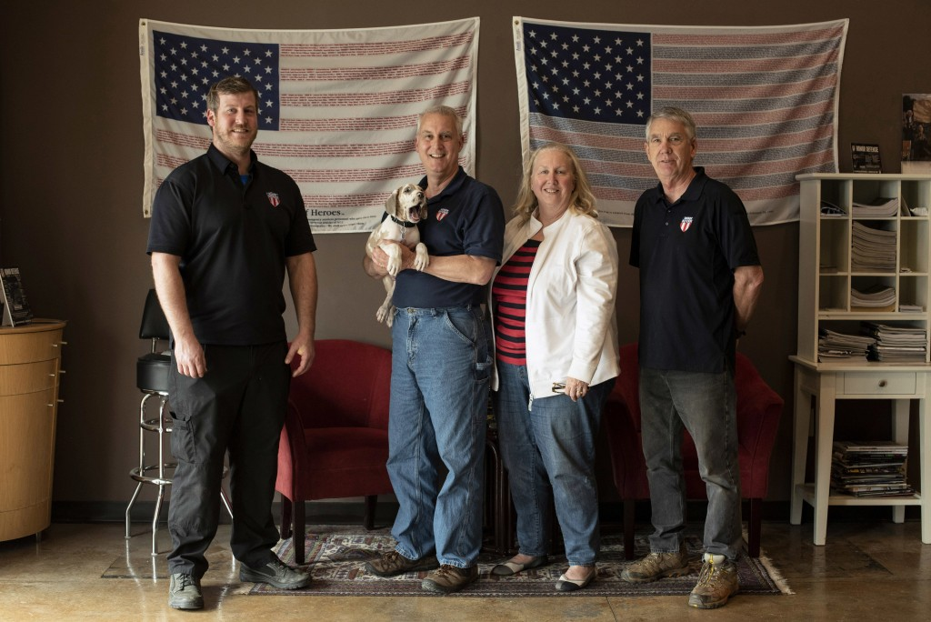 FILE - In this April 25, 2018, file photo, the owners and employees of Honor Defense, a gunmaker in Gainesville, Ga., pose in the company's lobby. Sta...