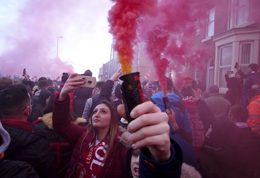 Football supporters set off flares before the English Premier League soccer match between Liverpool and Manchester United near Anfield Stadium in Live...