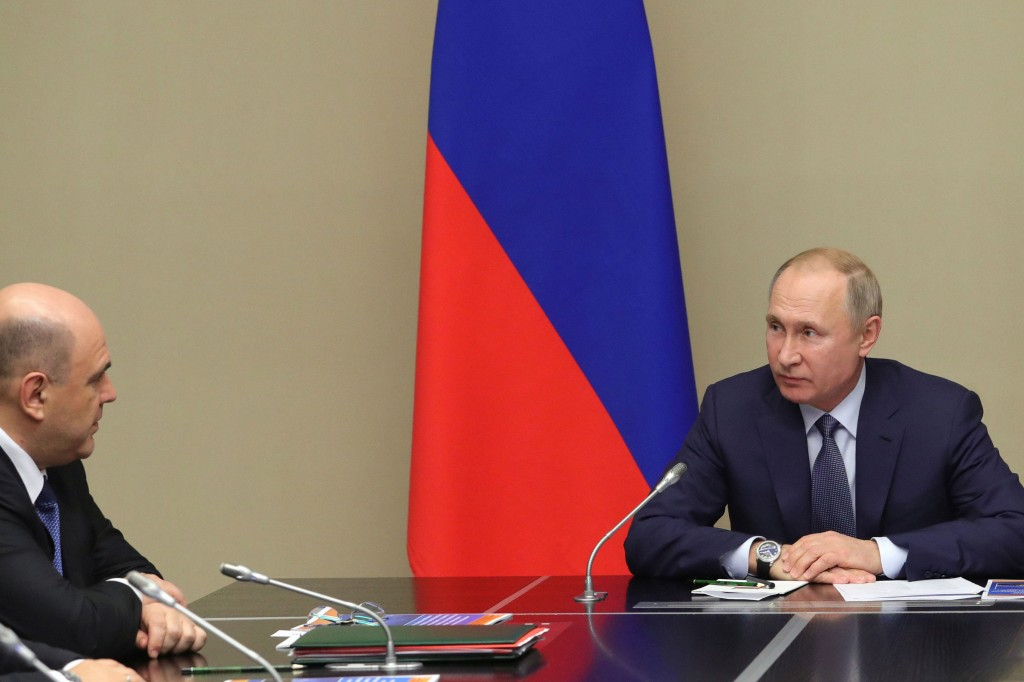 Russian President Vladimir Putin, right, and New Russian Prime Minister Mikhail Mishustin attend a Security Council meeting at the Novo-Ogaryovo resid...
