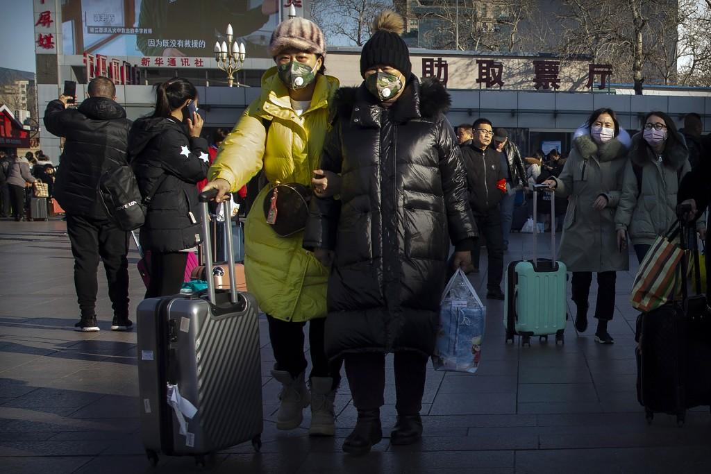 Travelers wear face masks as they walk outside of the Beijing Railway Station Jan. 20, 2020.