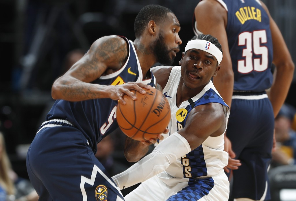 Denver Nuggets guard Will Barton, front, is stopped as he drives to the rim by Indiana Pacers guard Aaron Holiday in the first half of an NBA basketba...