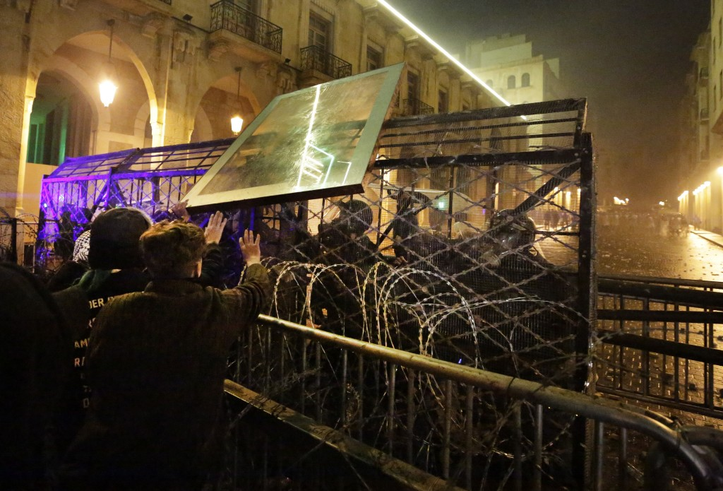 Anti-government protesters throw a glass panel against the riot police who are standing behind barriers defense, during ongoing protests against the p...