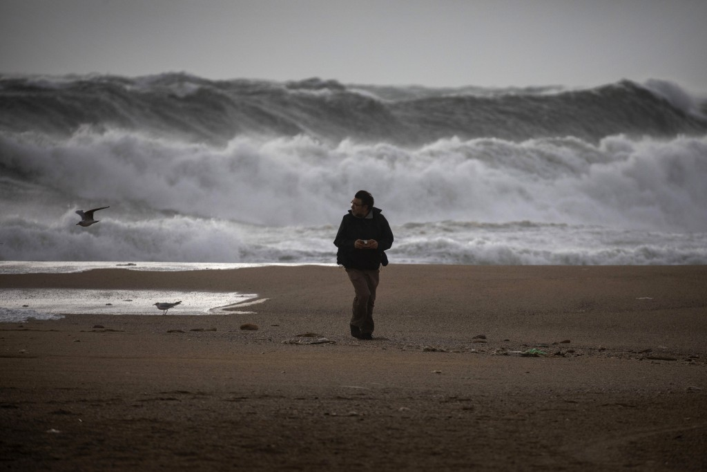 A man walks at the beach during strong winds in Barcelona, Spain, Monday, Jan. 20, 2020. Two people have died as storms carrying heavy snowfalls and g...