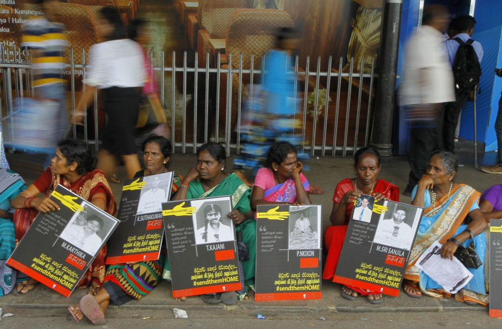 In this Monday, April 6, 2015, file photo, Sri Lankan ethnic Tamil women sit holding placards with portraits of their missing relatives as they protes...