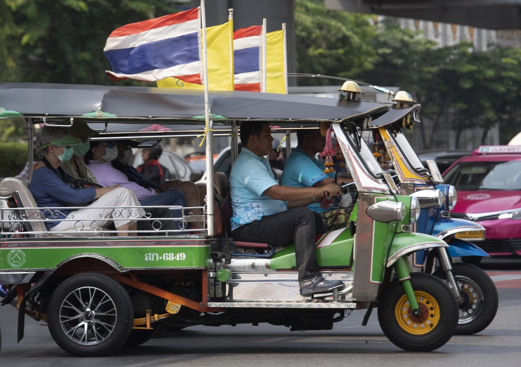 Tourists ride in tuk-tuks wearing face masks to protect from the poor air quality in Bangkok, Thailand, Monday, Jan. 20, 2020. Thick haze blanketed th...