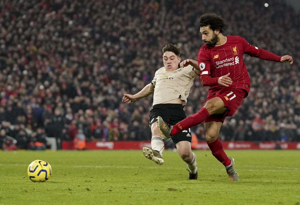 Liverpool's Mohamed Salah, right, shoots to score his side's second goal during the English Premier League soccer match between Liverpool and Manchest...