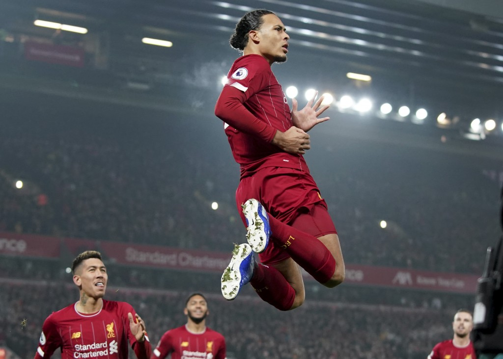 Liverpool's Virgil van Dijk jumps to celebrate scoring his side's first goal during the English Premier League soccer match between Liverpool and Manc...