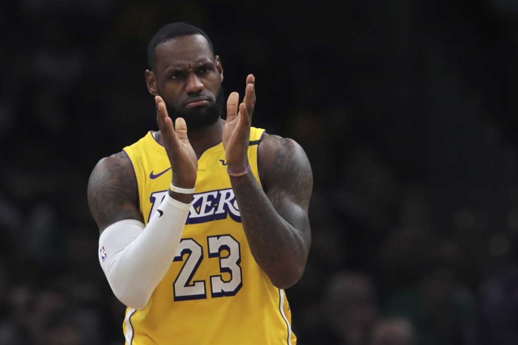 Los Angeles Lakers forward LeBron James applauds his teammates during the first half of an NBA basketball game against the Boston Celtics in Boston, M...
