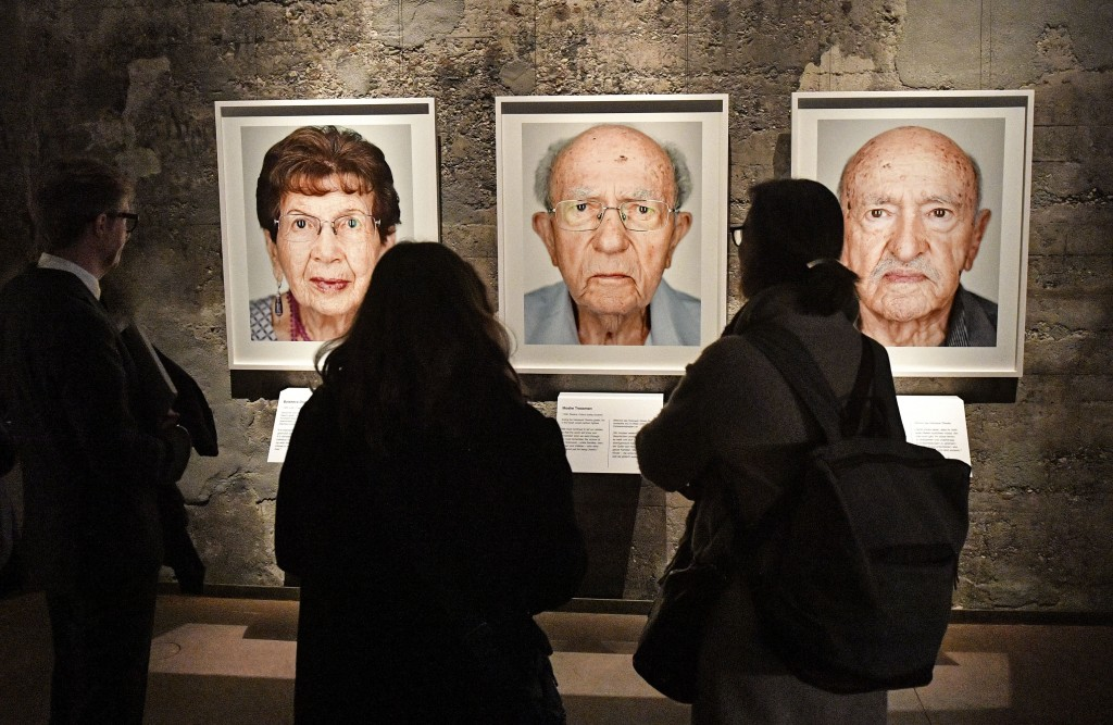 Visitors look at portrait photos of the exhibition 'Survivors - Faces of Life after the Holocaust' at the former coal mine Zollverein in Essen, German...