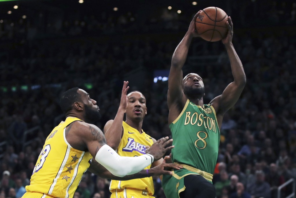 Boston Celtics guard Kemba Walker (8) drives to the basket past Los Angeles Lakers guard Avery Bradley (11) and forward LeBron James (23) during the f...