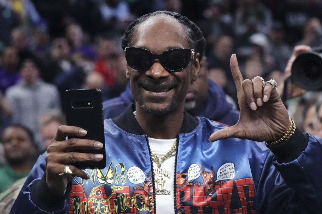 Rapper Snoop Dogg gestures to fans prior to the first half of an NBA basketball game between the Boston Celtics and Los Angeles Lakers in Boston, Mond...