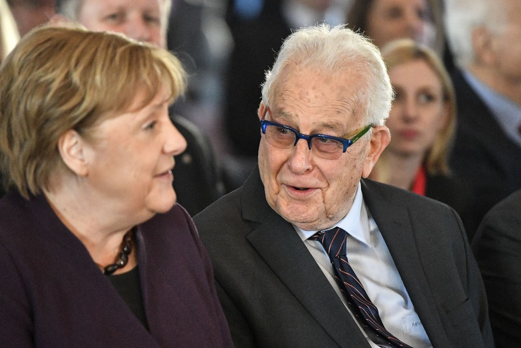 German chancellor Angela Merkel sits beside Holocaust survivor Naftali Furst, right, during the opening of the exhibition 'Survivors - Faces of Life a...