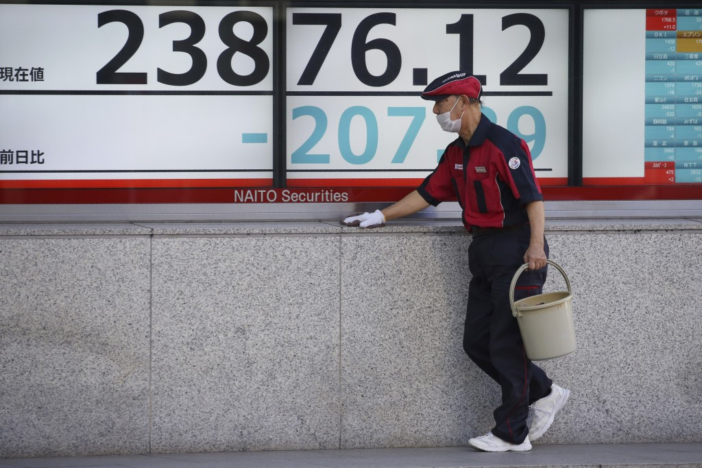 A worker cleans up an electronic stock board of a securities firm in Tokyo, Tuesday, Jan. 21, 2020. Asian stock markets have tumbled as concern about ...