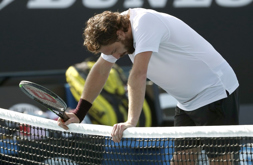 Latvia's Ernests Gulbis rests on the net, defeating Canada's Felix Auger-Aliassime in their first round singles match at the Australian Open tennis ch...