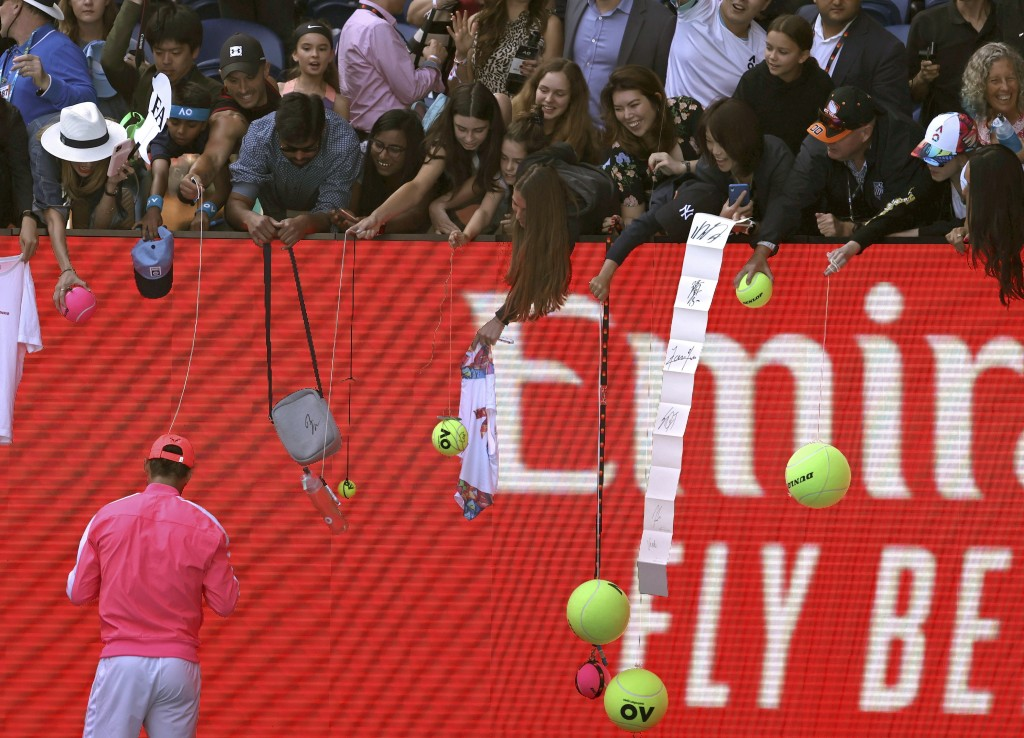 Spain's Rafael Nadal signs autographs after defeating Bolivia's Hugo Dellien in their first round singles match at the Australian Open tennis champion...