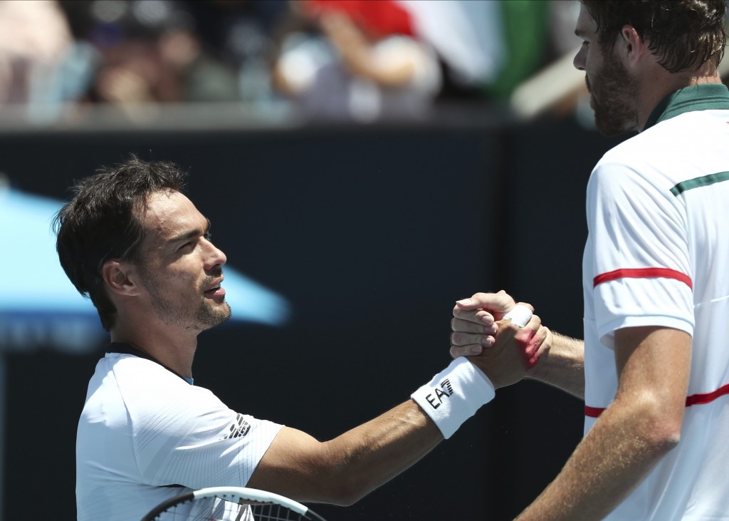 Italy's Fabio Fognini, left, is congratulated by Reilly Opelka of the U.S. after winning their first round singles match at the Australian Open tennis...