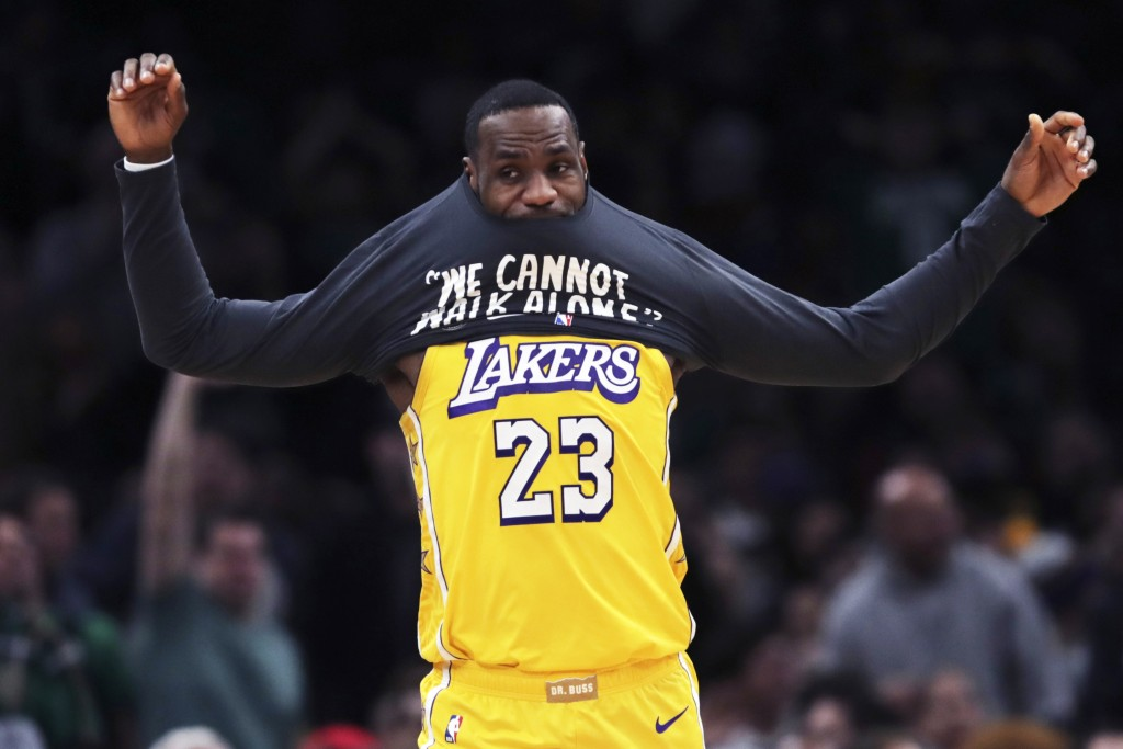 Los Angeles Lakers forward LeBron James puts on a warm-up shirt as he goes to the bench during the first half of an NBA basketball game against the Bo...