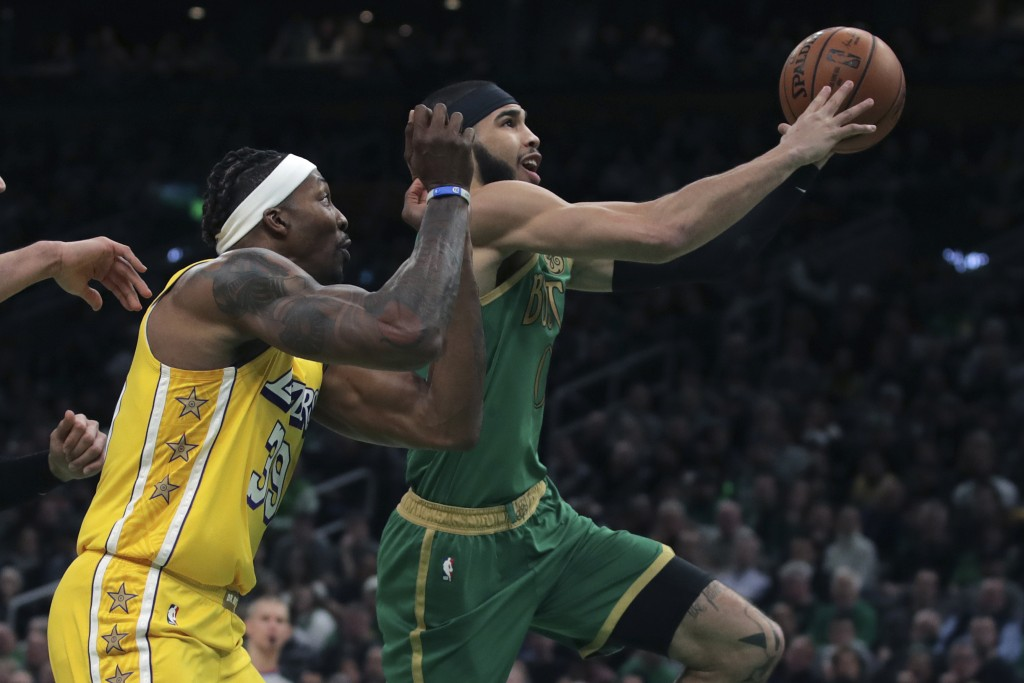 Boston Celtics forward Jayson Tatum, right, drives past Los Angeles Lakers center Dwight Howard (39) during the first half of an NBA basketball game i...