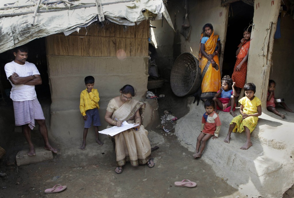 In this Thursday, April 1, 2010, file photo, Mahesh Shah, left, stands as his family members watch while a census worker Rumima Das, center, writes th...