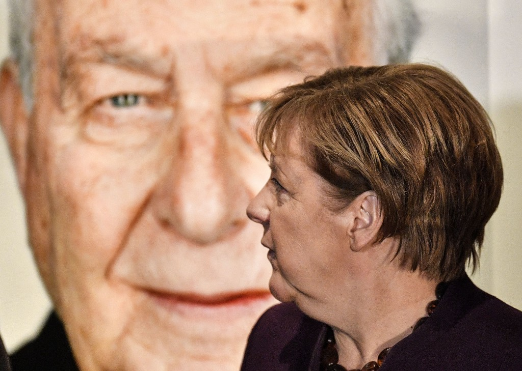 German chancellor Angela Merkel stands in front of a portrait of Holocaust survivor Naftali Furst during the opening of the exhibition 'Survivors - Fa...
