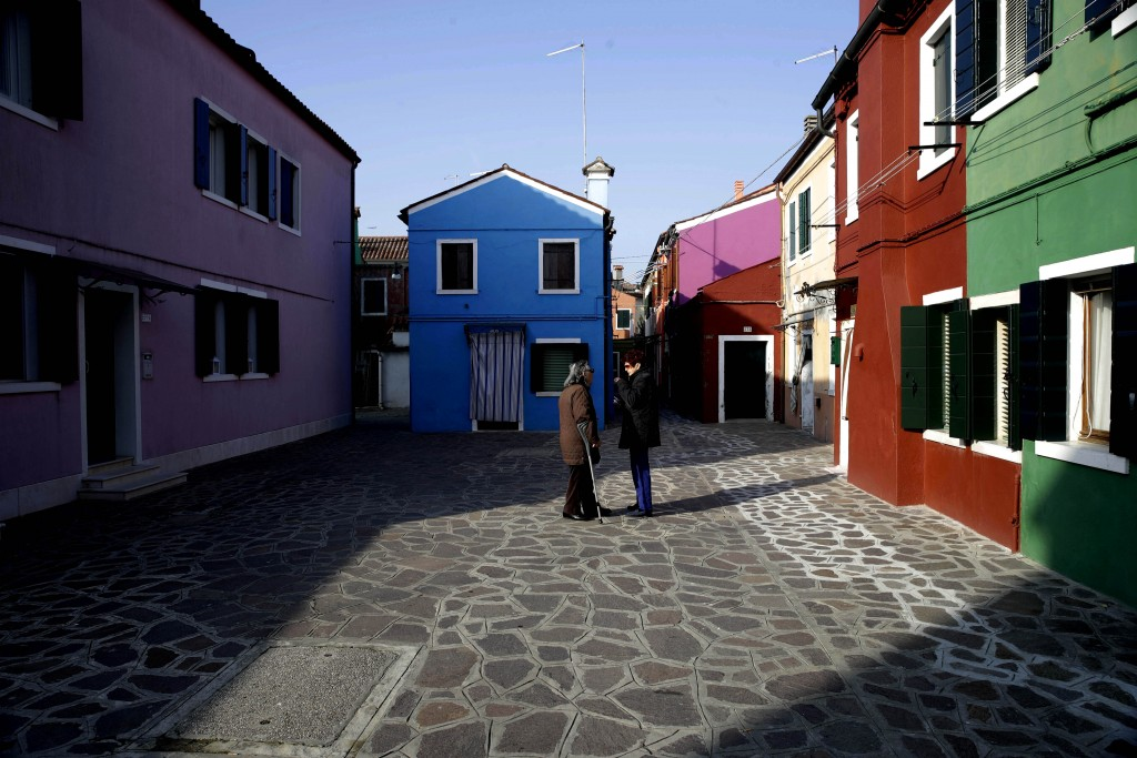 In this image taken on Thursday, Jan. 16, 2020, two women stalk in a small square of the Burano island, Italy. The Venetian island of Burano's legacy ...