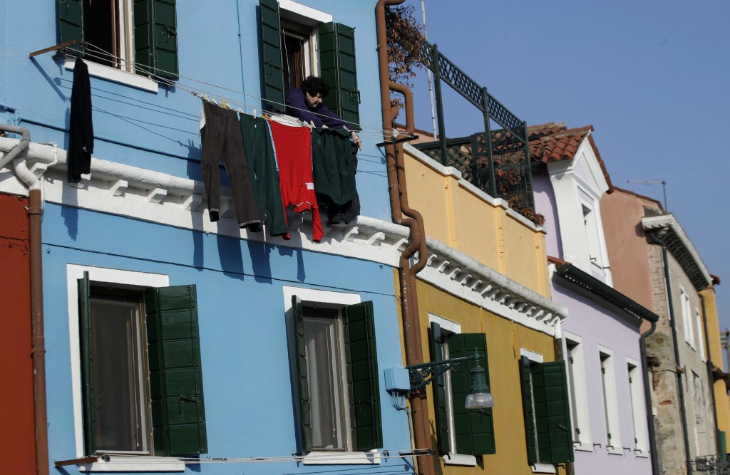 In this image taken on Thursday, Jan. 16, 2020, an elderly woman hangs laundry outside a window, at the Burano island, Italy. The Venetian island of B...