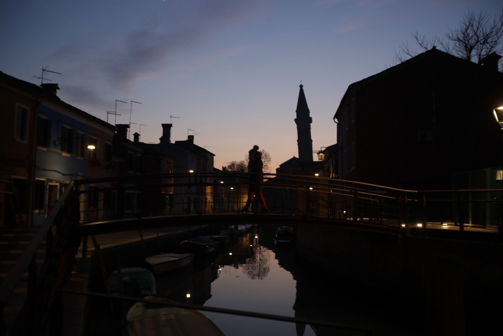 In this image taken on Thursday, Jan. 16, 2020, a woman walks over a bridge at sunset, at the Burano island, Italy. The Venetian island of Burano's le...