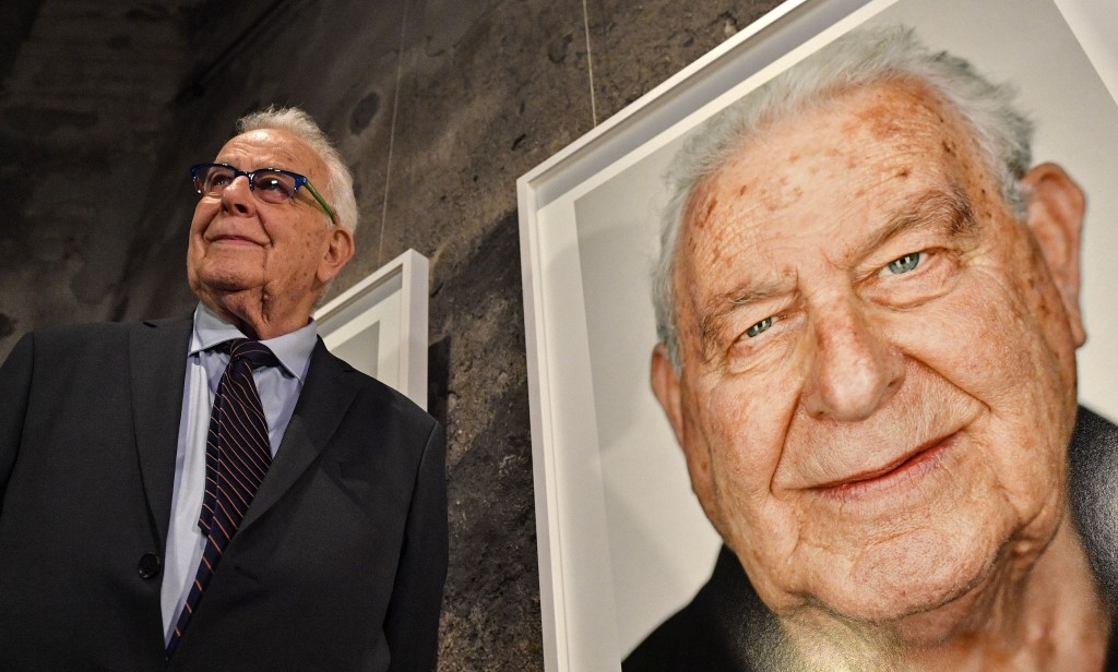 Holocaust survivor Naftali Furst stands next to his portrait during the opening of the exhibition 'Survivors - Faces of Life after the Holocaust' at t...