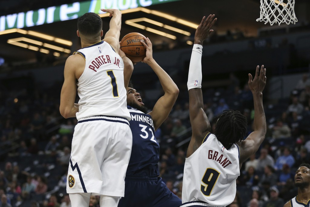 Minnesota Timberwolves' Karl-Anthony Towns shoots the ball against Denver Nuggets' Michael Porter Jr. and Jerami Grant in the first half of an NBA bas...