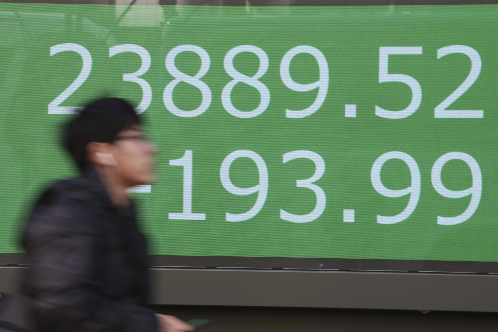 A man walks by an electronic stock board of a securities firm in Tokyo, Tuesday, Jan. 21, 2020. Asian stock markets have tumbled as concern about the ...