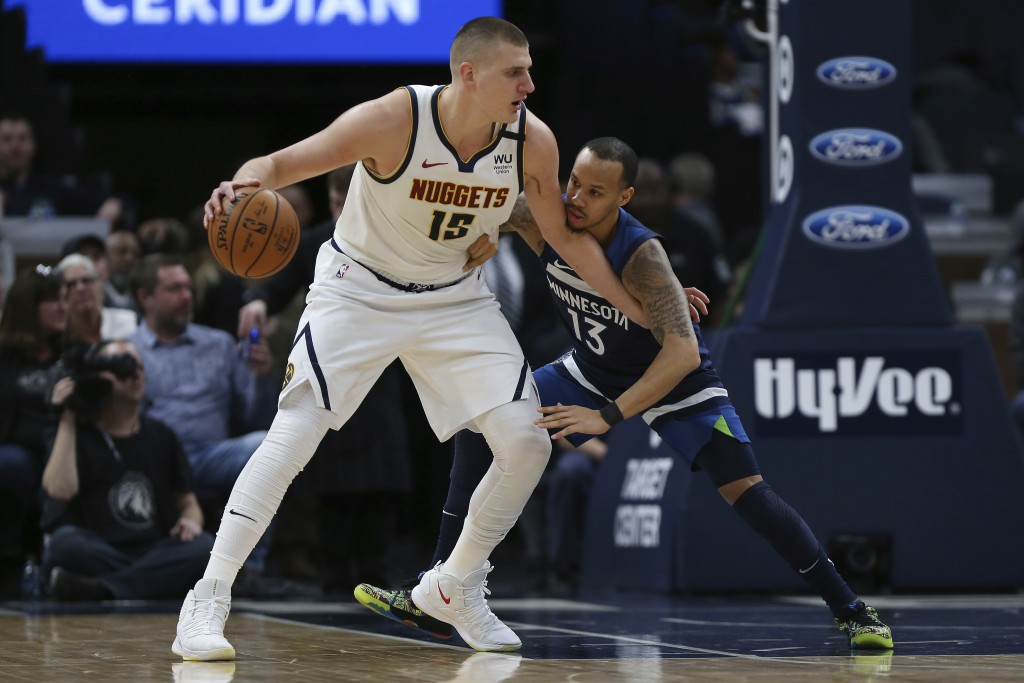 Denver Nuggets' Nikola Jokic controls the ball against Minnesota Timberwolves' Shabazz Napier in the first half of an NBA basketball game Monday, Jan....