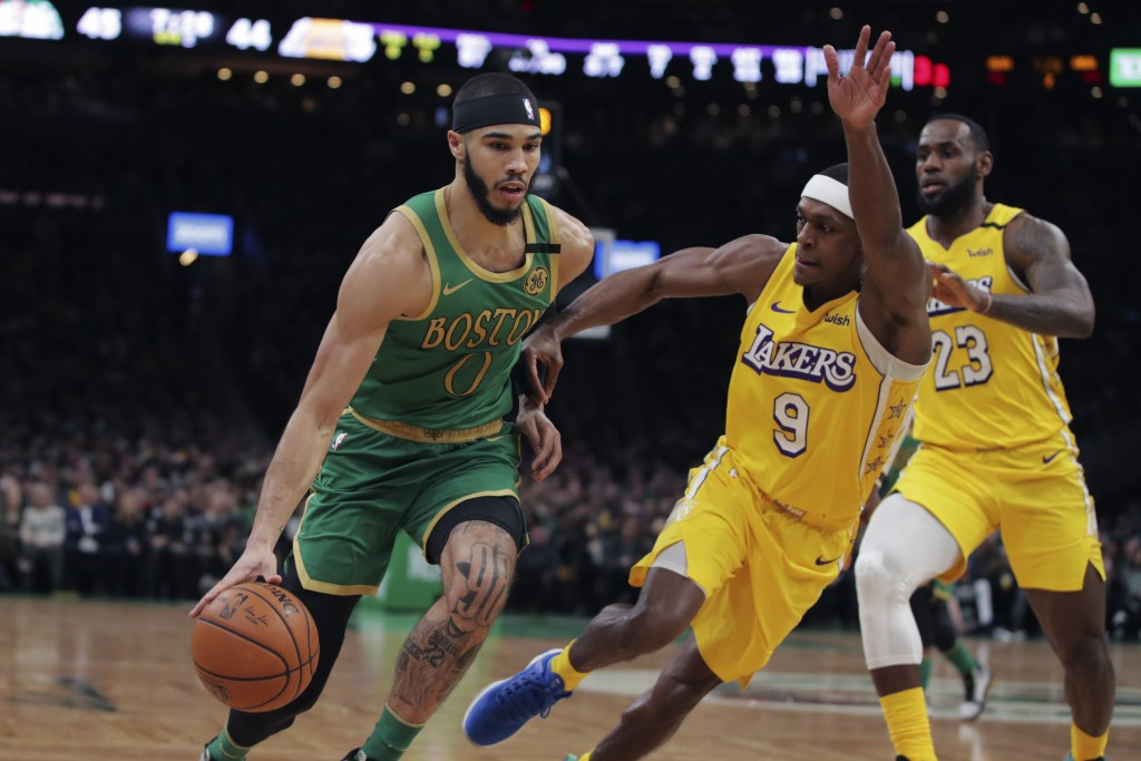 Boston Celtics forward Jayson Tatum (0) drives to the basket against Los Angeles Lakers guard Rajon Rondo (9) and forward LeBron James (23) during the...