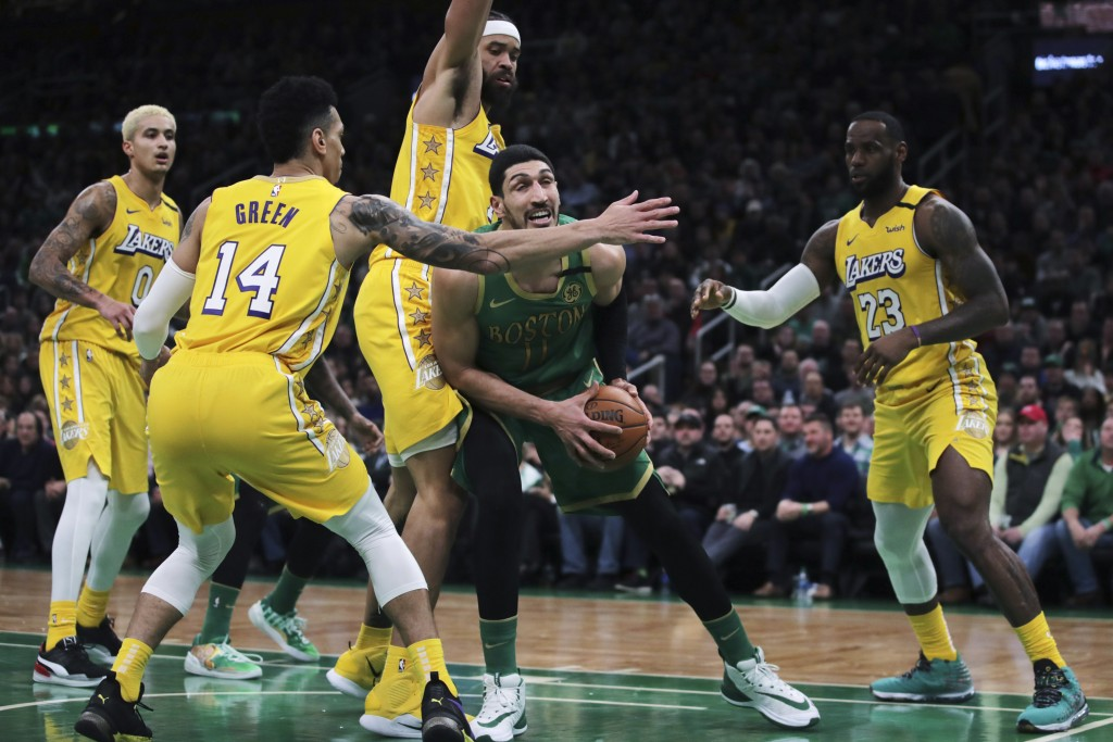Boston Celtics center Enes Kanter (11) is surrounded by Los Angeles Lakers as he tries to follow his rebound with a shot during the first half of an N...