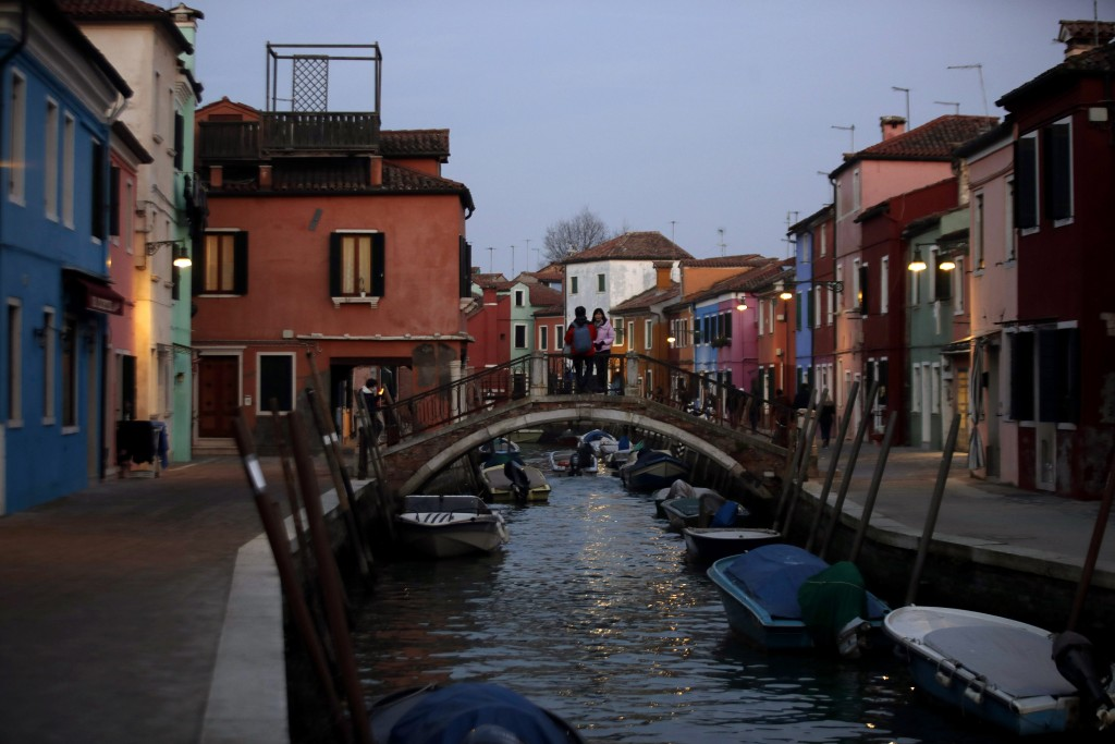 In this image taken on Thursday, Jan. 16, 2020, people stand on a bridge at the Burano island, Italy. The Venetian island of Burano's legacy as a fish...