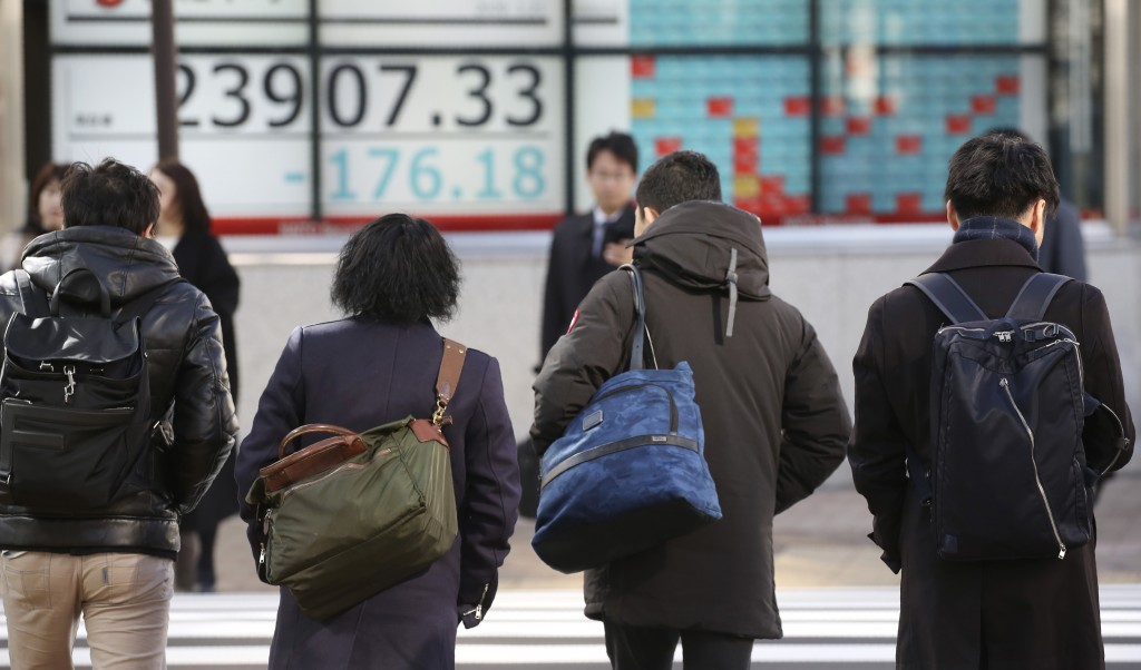 People walk by an electronic stock board of a securities firm in Tokyo, Tuesday, Jan. 21, 2020. Asian stock markets have tumbled as concern about the ...