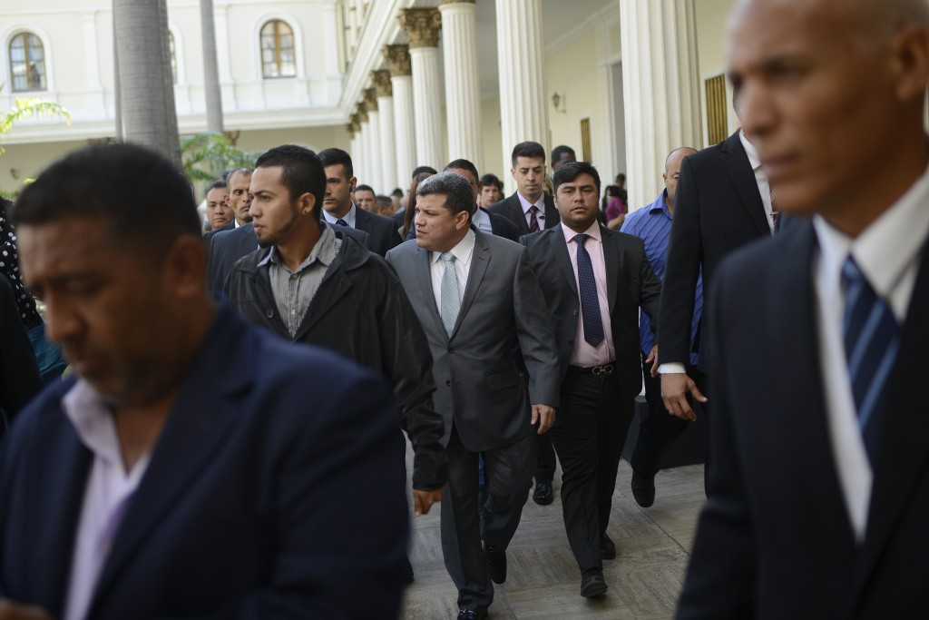 Lawmaker Luis Parra, center, who broke with opposition leader Juan Guaido and claims the presidency of the National Assembly, leaves after leading a s...