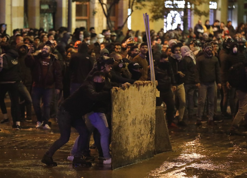 Anti-government protesters hide behind a wood barrier as they clash with the riot police during a protest against the new government, near the parliam...