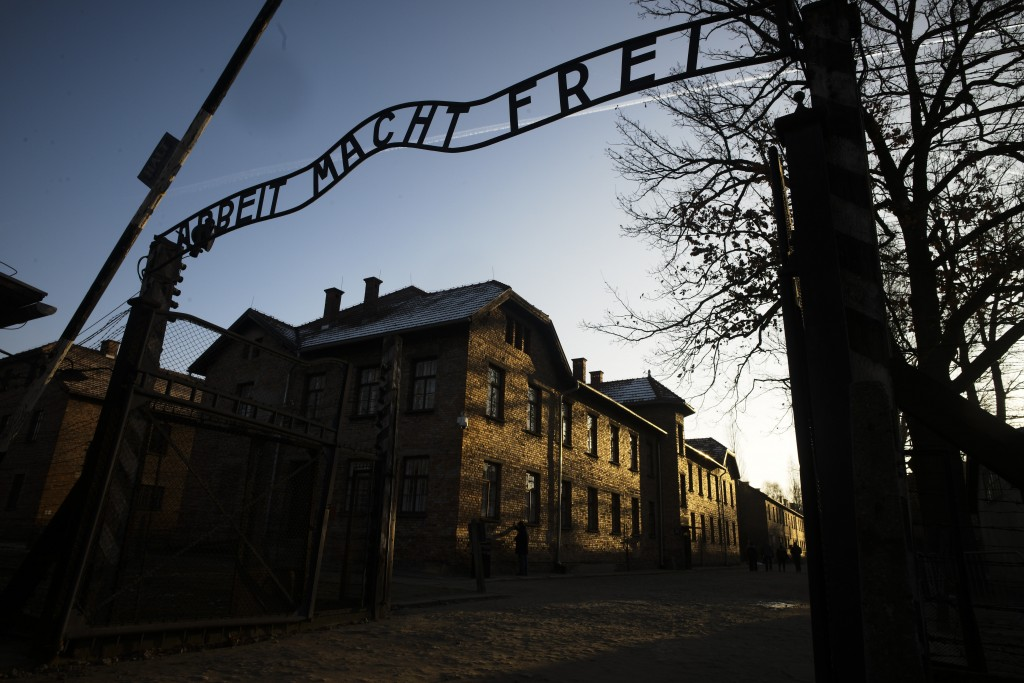 FILE - In this Dec. 6, 2019, file photo, the sun lights the buildings behind the entrance of the former Nazi death camp of Auschwitz-Birkenau in Oswie...