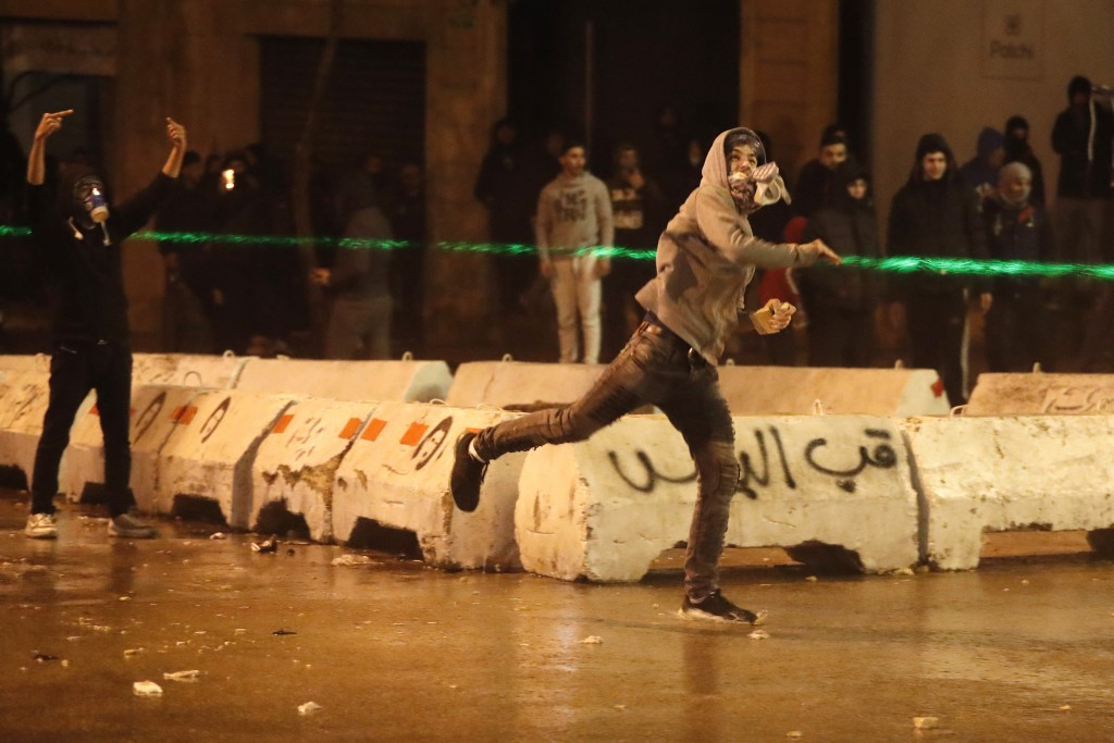 An anti-government protester throws stones at the riot police during a protest against the new government, near the parliament square, in Beirut, Leba...