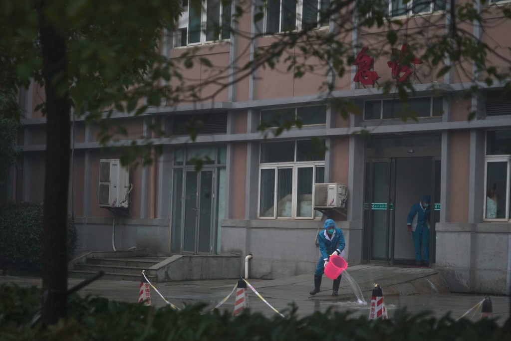 Hospital staff wash the emergency entrance of Wuhan Medical Treatment Center, where some infected with a new virus are being treated, in Wuhan, China,...