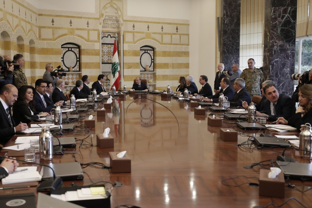 President Michel Aoun, center, speaks with Prime Minister Hassan Diab, center left, during the cabinet meeting at the presidential palace in Baabda, e...