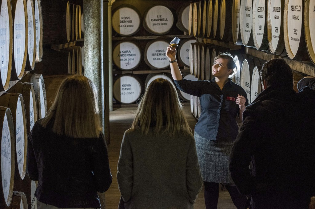 People are guided during a cellar tour of the Dewer's Distillery in Aberfeldy, the Scottish Highlands, in 2018, where they have produced Scotch whisky...